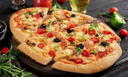 Delicious seafood shrimps and mussels pizza on a black wooden table. Italian food.